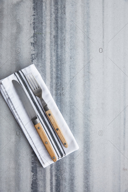 Fork and knife with linen napkin on a marble surface