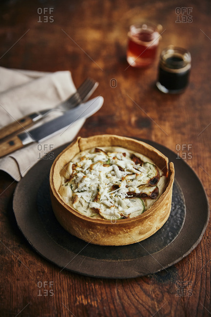 A baked zucchini tart with fork and knife on a rustic surface