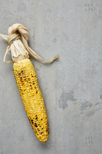 Grilled corn cob on gray surface