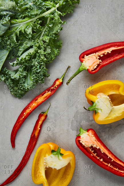 Horizontally cut yellow and red peppers with fresh kale