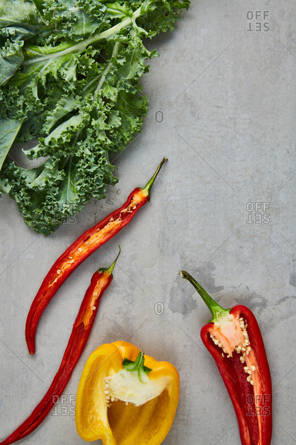 Top view of cut yellow and red peppers with fresh kale
