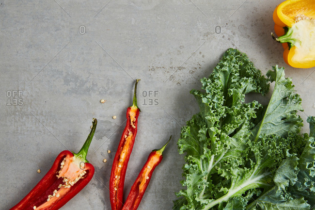 Top view of cut yellow and red peppers with fresh kale on gray surface