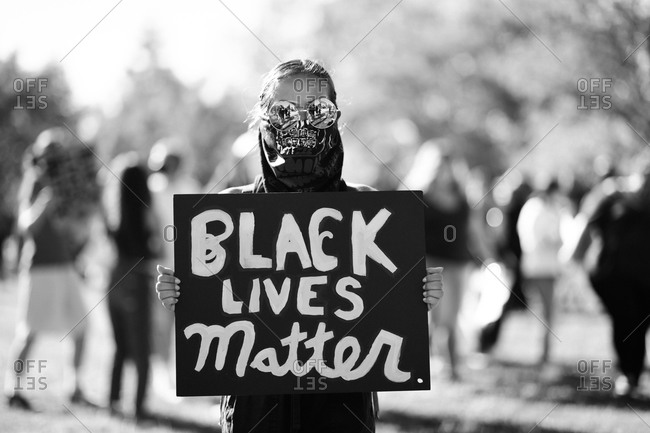 Young woman marching with sign for the Black Lives Matter movement