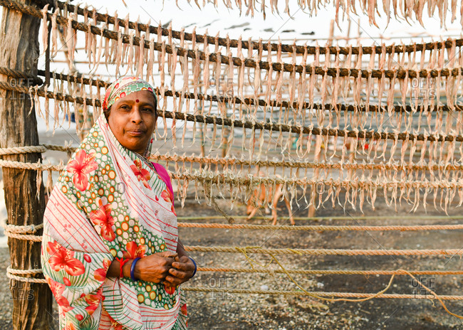 Udvada, India - September 9, 2020: Portrait of an Indian woman standing by rack of drying fish