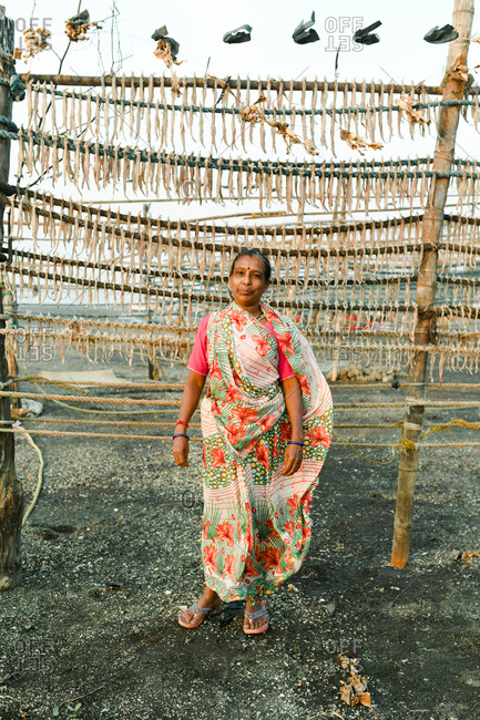 Udvada, India - September 9, 2020: Indian woman in a colorful sari standing by rack of drying fish
