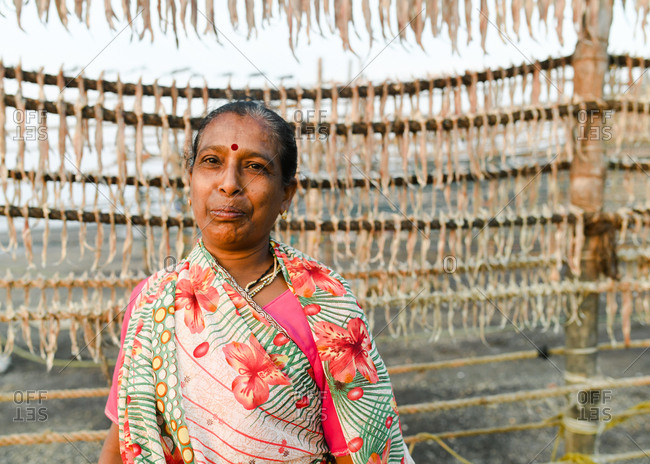 Udvada, India - September 9, 2020: Close up of an Indian woman standing by rack of drying fish