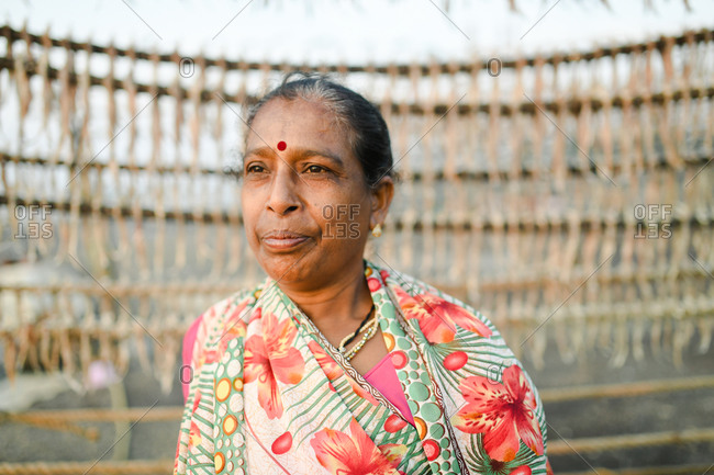 Udvada, India - September 9, 2020: An Indian woman standing by rack of drying fish