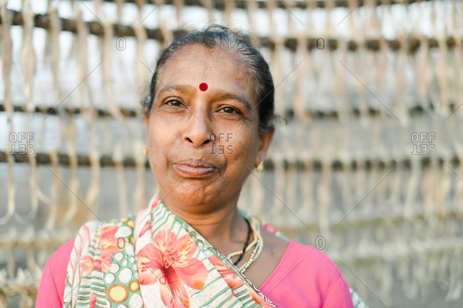 Udvada, India - September 9, 2020: Close up portrait of an Indian woman standing by rack of drying fish