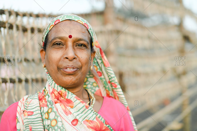 Udvada, India - September 9, 2020: Portrait of an Indian woman wearing a colorful sari and standing by rack of drying fish