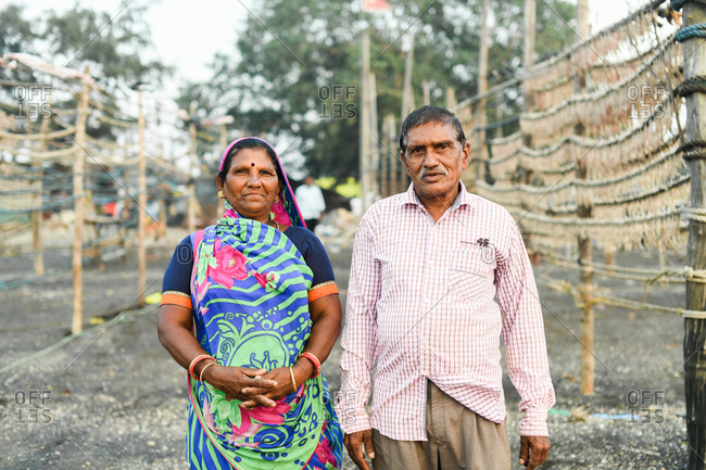 Udvada, India - September 9, 2020: Indian couple standing by racks of drying fish