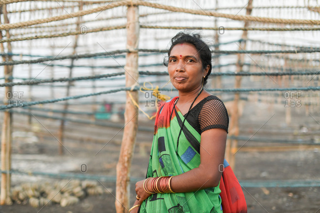 Udvada, India - September 9, 2020: Indian woman standing by drying racks in a fishery