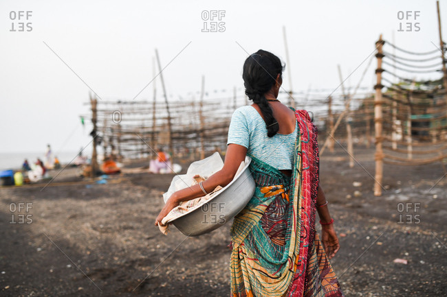 Rear view of Indian woman carrying bowl outdoors in a fishery in Udvada, India
