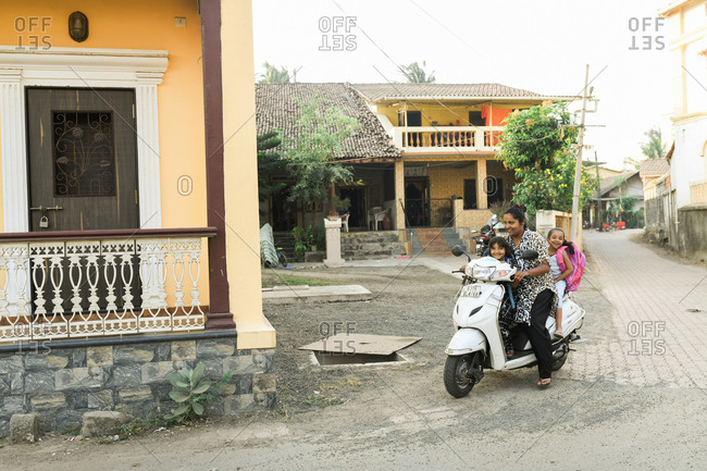 Udvada, India - September 9, 2020: Mother and two children riding on a scooter in town