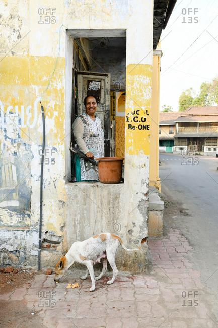 Udvada, India - September 9, 2020: Woman feeding stray dog food scraps from porch