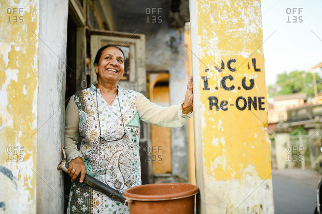 Udvada, India - September 9, 2020: Portrait of a local woman standing on porch looking away and smiling