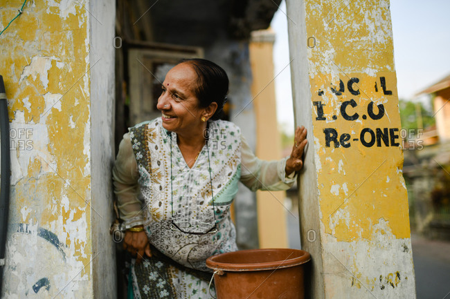 Udvada, India - September 9, 2020: Local woman standing on porch looking over railing and smiling