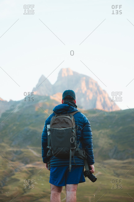 Young caucasian hiker holding a camera enjoying the view of a big mountain peak during sunset