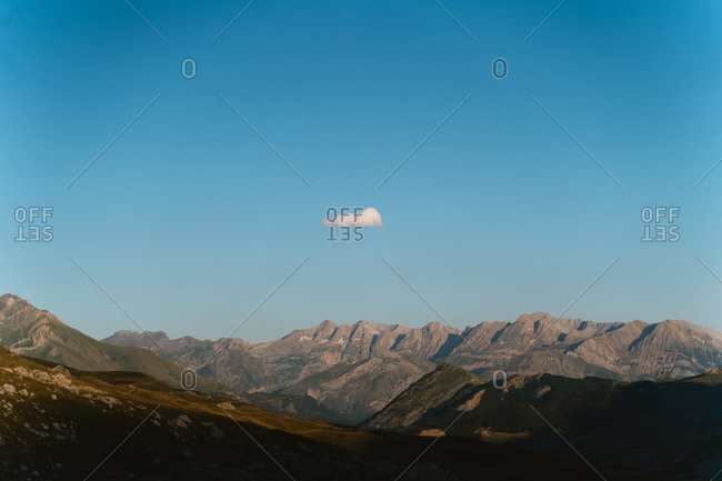 Pyrenees mountain range on a sunny day with a single cloud in the blue sky