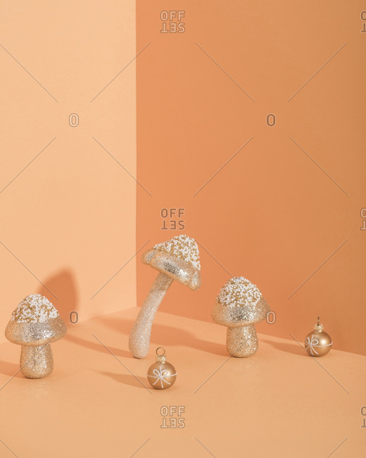 Bright mushrooms ornaments with golden sparkle for Christmas with orange background