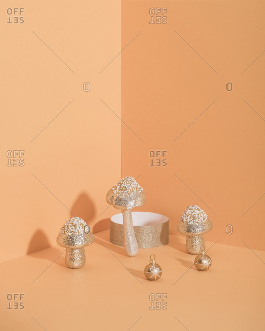 Golden sparkles ornaments for Christmas tree with orange background and copy space