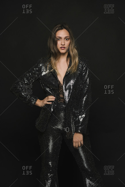 Woman demonstrating power in a black sequin suit for a party