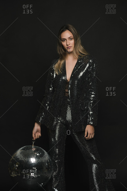 Elegant woman holding a disco ball at a New Year's Eve party