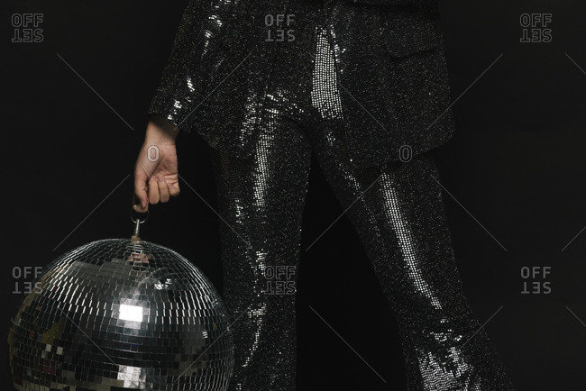 Faceless person wearing a sequin suit holding a disco ball