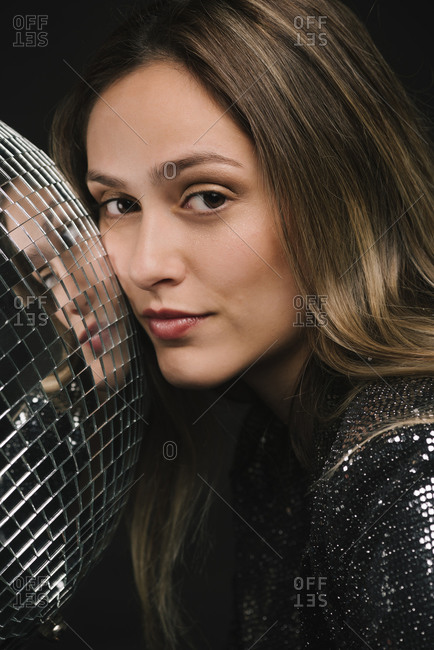 Happy woman with a disco ball, close-up portrait