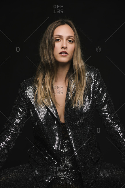Blonde woman in a black sequin suit for a party