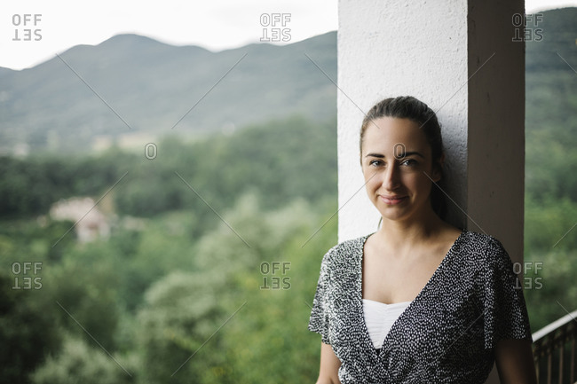 Portrait of beautiful woman on terrace with landscape of mountains in the background
