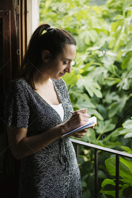 Woman taking note on a notebook while leaning on balcony at home