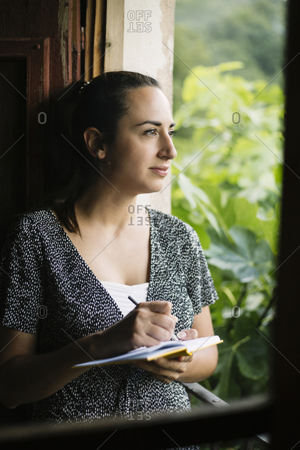 Pensive woman leaning on balcony while taking notes on a notebook