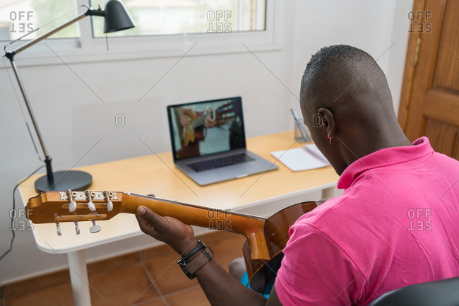 Young African-American man learning to play the guitar during an online class