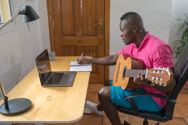 Side view of young African-American man taking notes at an online guitar lesson