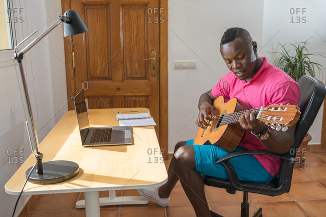 Side view of African American male musician in casual wear sitting on a chair and playing acoustic guitar in living room