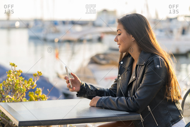 Happy young woman sitting on the terrace while she checks her cell phone during sunset