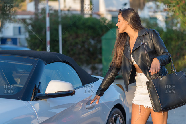 Elegant young woman about to open the door of her luxurious car