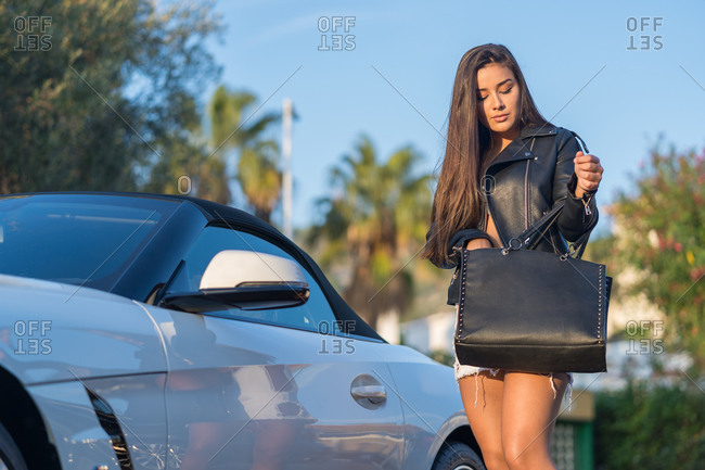 Pretty young woman standing and looking keys of her luxurious car in her bag outdoors