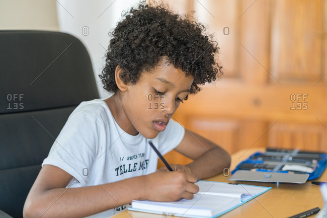 A male black child doing homework at home