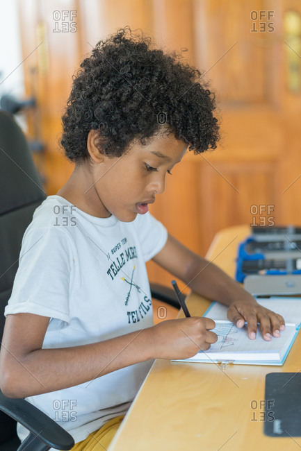 Afro-haired boy does his homework at home