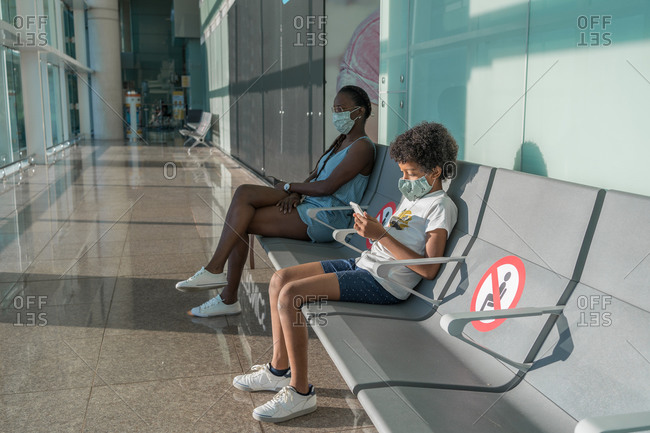 African American mother and son wearing face masks while waiting in airport