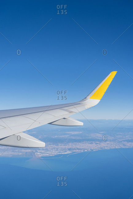 Looking over aircraft wing in flight about the port of Barcelona, Catalonia, Spain. Vertical shoot