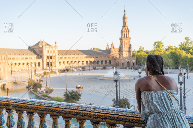 African-American woman on the balcony looking at old buildings in Seville, Spain