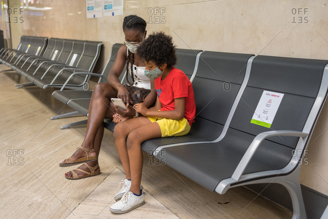 African American mother and son wearing face masks while looking at a phone at the airport