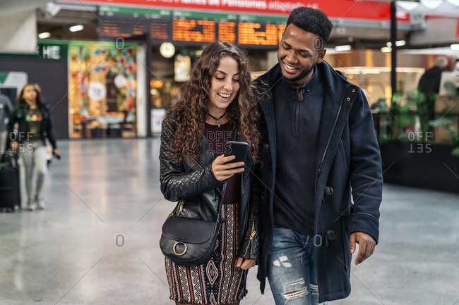 Happy moment of interracial couple using phone in train station.