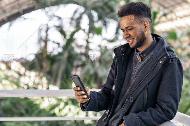 African American man using his cellphone and smiling.