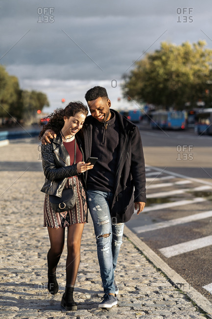 Happy interracial couple looking at a phone while walking