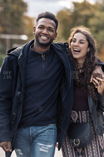 Happy interracial couple walking together in Madrid city
