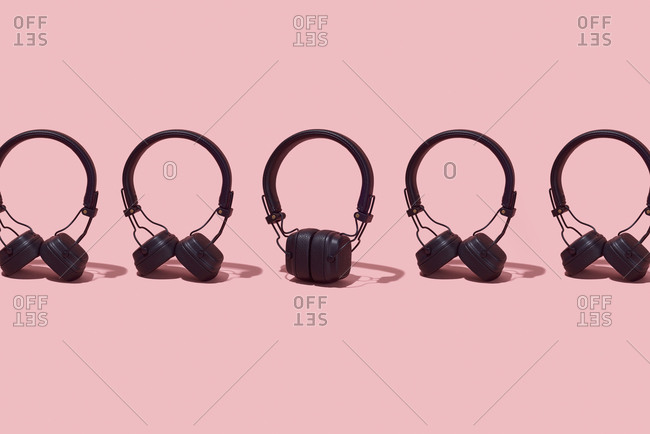 Black wireless headphones arranged in a line on a pink background
