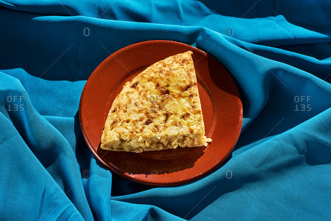 Spanish omelet in a brown earthenware plate, on a wrinkled blue fabric